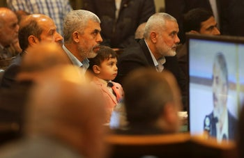 Yahya Sinwar holds his son Ibrahim while he listens to Khaled Mashaal, the outgoing Hamas leader in exile, during his news conference in Doha, Qatar, on Monday, May 1, 2017