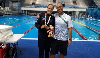 Anastasia Gorbenko (left) with her coach Ehud Segal and the gold medal