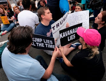 A pro-Trump supporter sitting with protesters demonstrating against the Senate confirmation of Brett Kavanaugh to the Supreme Court, Washington October 6, 2018.