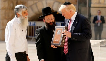 U.S. President Donald Trump receiving a book of psalms after leaving a note at the Western Wall in Jerusalem, May 22, 2017 (illustrative).