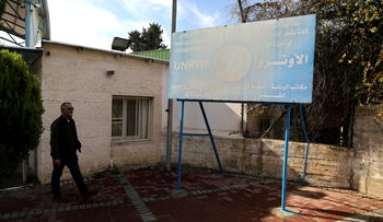 A man walks next to a sign at the entrance to the UNRWA West Bank Field Office complex in East Jerusalem, January 3, 2018.