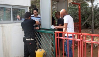Workers undergo a security check at the Barkan industrial zone, West Bank, October 8, 2018.