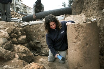 Danit Levy, of the Israel Antiquities Authority, with the stone bearing the most ancient inscription ever found with the full name of Jerusalem appearing as it is spelled today, at a Jerusalem salvage excavation near the city's entrance, October 2018.