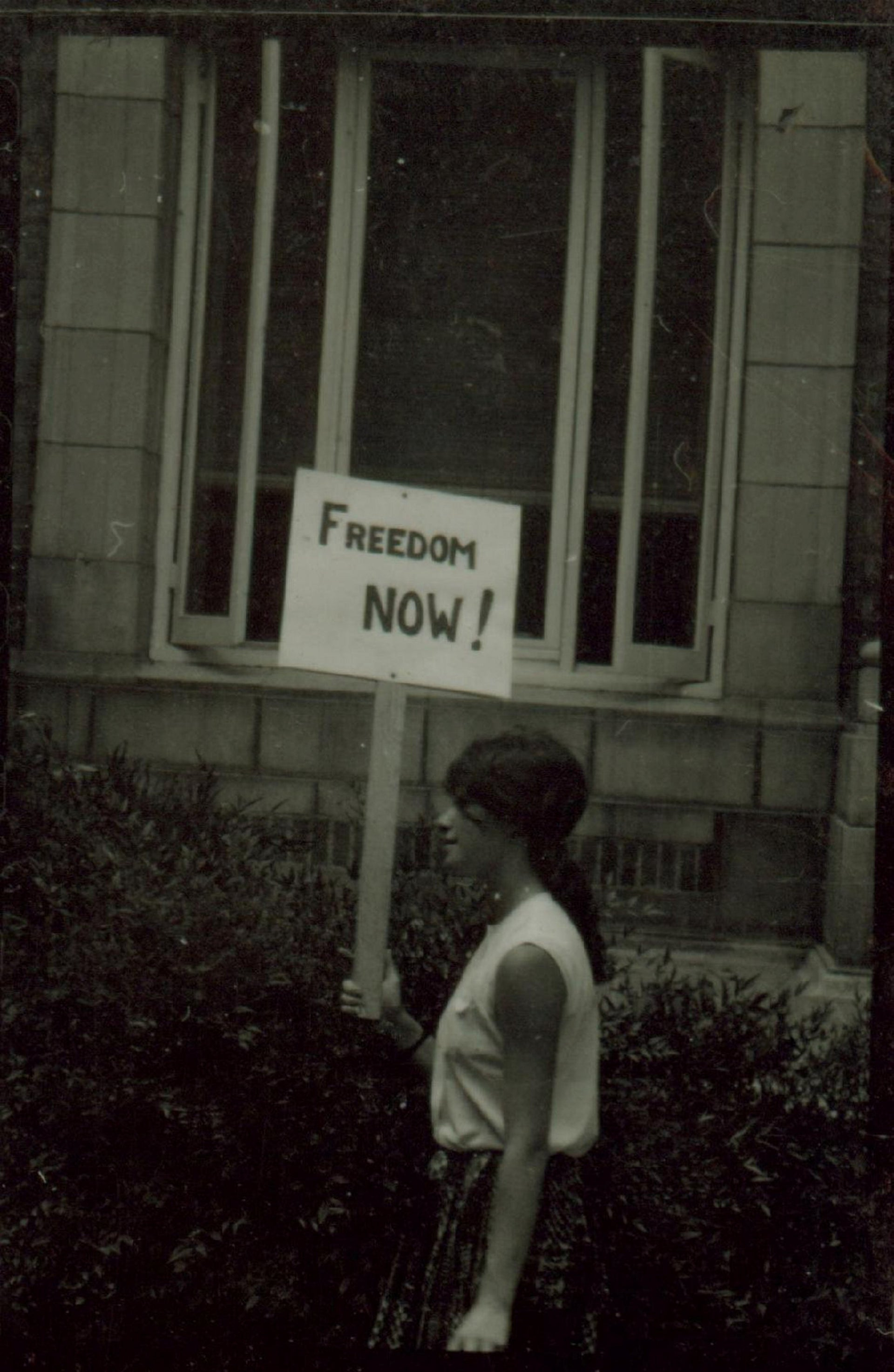 Heather Booth holding a sign while demonstrating in Shaw, Mississippi, when she went to register voters in 1964.