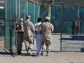 U.S. Navy guards escort a detainee through Camp Delta at Guantanamo Bay naval base, June 10, 2008.