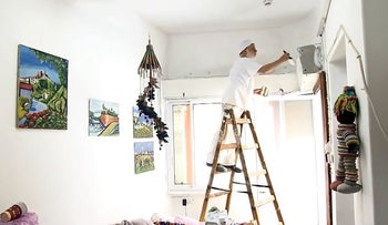 A volunteer for Saxon Friends of Israel helps paint the home of a Holocaust survivor
