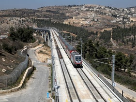 The Palestinian village of Beit Iksa in the West Bank is seen in the background as Israel's new high-speed rail line travels on its tracks in Jerusalem September 25, 2018.