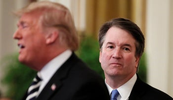 U.S. President Donald Trump speaks next to U.S. Supreme Court Associate Justice Brett Kavanaugh as they participate in a ceremonial public swearing-in in the East Room of the White House in Washington, U.S., October 8, 2018.