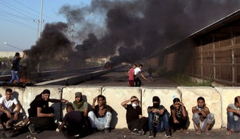 Palestinian protesters rest behind concrete blocks as others hurl stones at Israeli soldiers during a protest at the entrance of Erez border crossing in the northern Gaza Strip, Sept. 26, 2018.