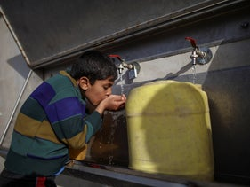 A Palestinian boy drinks water from public taps at the al- Shati refugee camp in Gaza city, March 7 2018.