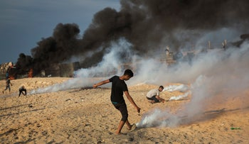 Palestinian protesters cover teargas canisters fired by Israeli troops during a protest on the beach at the border with Israel near Beit Lahiya, northern Gaza Strip, October 15, 2018.