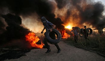 Palestinian protesters carry tires as smoke billows during a protest along the Israel-Gaza border, October 12, 2018.