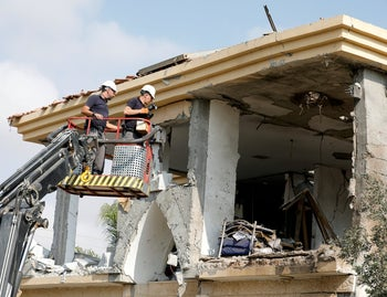 Israeli sappers stand on a crane as they work on a house that the Israeli military said was hit by a rocket fired from the Gaza Strip, in Beersheba, southern Israel October 17, 2018.