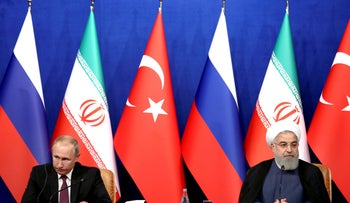 Iran's President Hassan Rouhani, right, speaks in a joint press conference with Russia's President Vladimir Putin, left, and Turkey's President Recep Tayyip Erdogan in Tehran, Iran, Sept. 7, 2018.