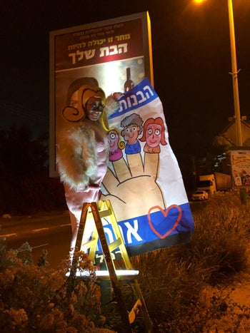 The Israeli artist Shoshke posts over a Habayit Hayehudi poster with a sign that says 'The daughters of Ramle.'