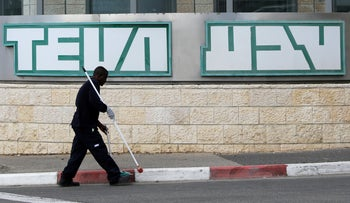 A man cleans near the logo of Teva Pharmaceutical Industries at their plant in Jerusalem, December 14, 2017.