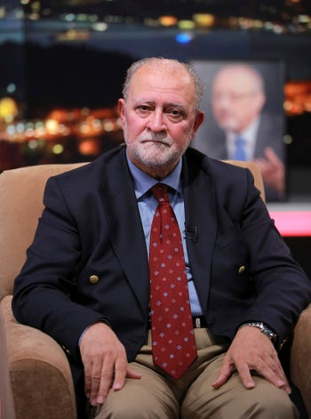Azzam Tamimi, close friend of Jamal Khashoggi, sits next to an empty chair with his picture placed on it, on a program for TV station al-Hewar in which Khashoggi was due to appear. Istabul, Oct. 11, 2018