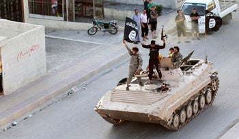 FILE PHOTO: Militant Islamist fighters take part in a military parade along the streets of northern Raqqa province, Syria, June 30, 2014.