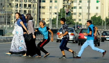 In this Aug. 20, 2012 file photo, an Egyptian youth, trailed by his friends, gropes a woman crossing the street with her friends in Cairo, Egypt.