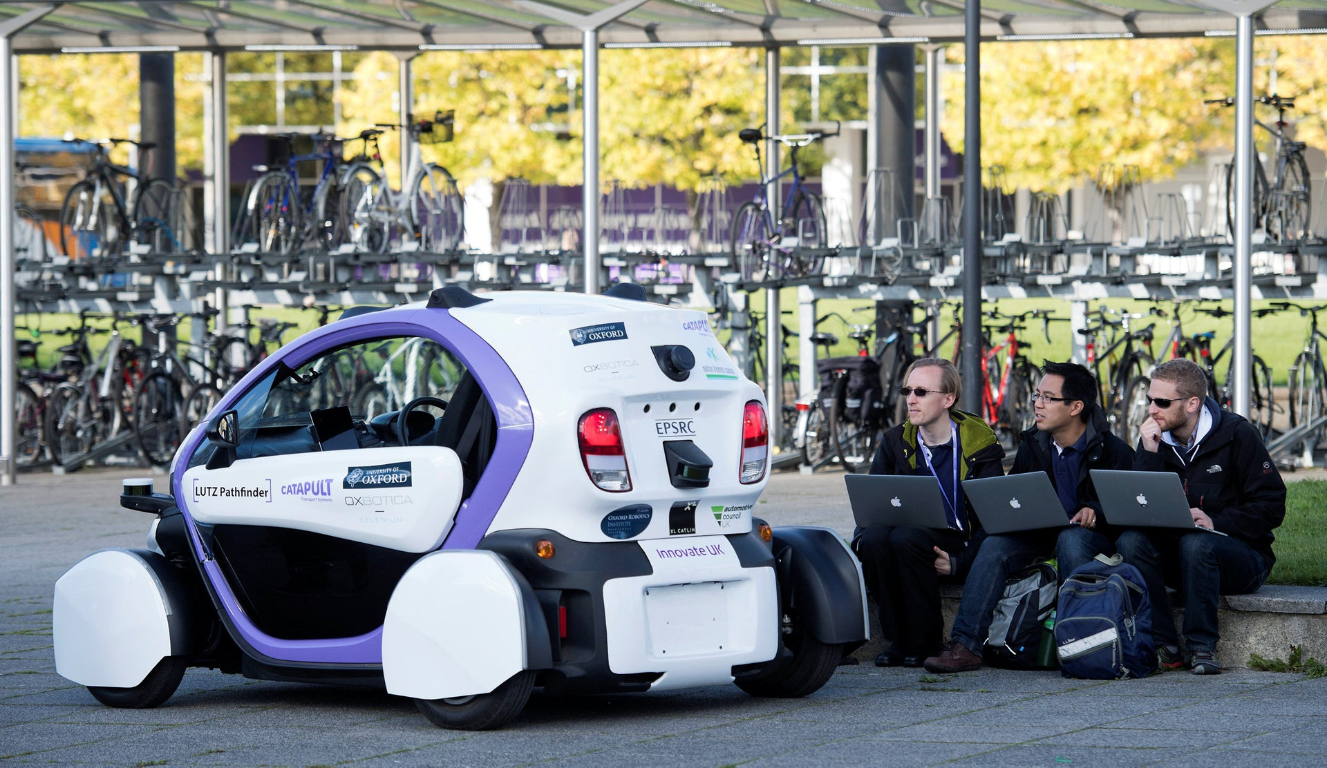 Technicans analise data follwong the trial of an autonomous self-driving vehicle in a pedestrianised zone, during a media event in Milton Keynes, north of London, on October 11, 2016