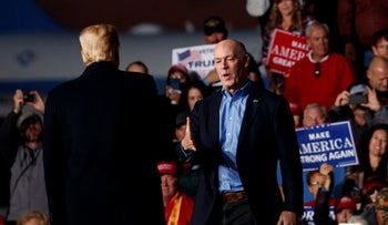 Rep. Greg Gianforte, R-Mont., is greeted on stage by President Donald Trump during a campaign rally at Minuteman Aviation Hangar, Thursday, Oct. 18, 2018