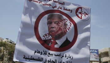 Placard picturing U.S. President Donald Trump with the Arabic slogans: 'US policy is shameful to humanity' and 'Trump's visit peddles illusions and ignores Palestinian rights.' West Bank's Qalandia checkpoint, May 22, 2017