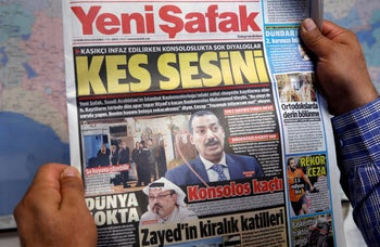 """A man holds Yeni Safak newspaper with a headline that reads """" (To the Saudi consul) Shut up """" in Ankara, October 17, 2018."""