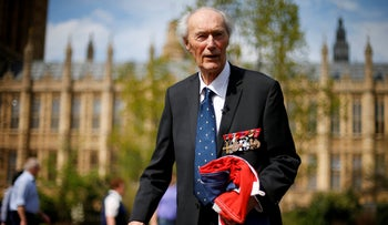 File photo: WWII Norwegian resistance fighter Joachim Roenneberg holds up a Union flag after it was presented to him by the Clerk of the House of Lords in Westminster, London, 2013.