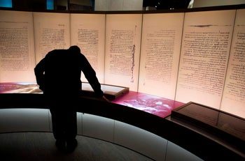 Visitors look at an exhibit about the Dead Sea scrolls during a media preview of the Museum of the Bible in Washington, D.C., November 14, 2017.