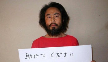 Japanese freelance journalist Jumpei Yasuda holds a banner with a handwritten message in Japanese at an undisclosed location, released May 30, 2016