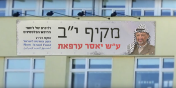 A still from the film, 'When Ahmed Tibi is Prime Minister,' showing 'Yassar Arafat Highschool.'  The banner reads 'in memory of the Palestinian freedom fighters, funded by the New Israel Fund'