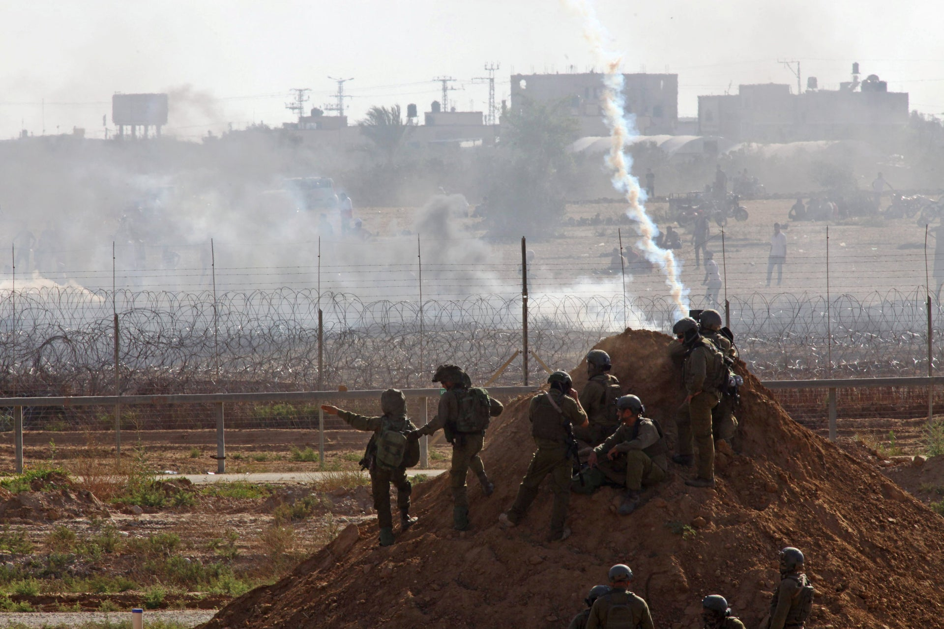 Israeli soldiers and Gaza protesters face off on the border, June 2018.
