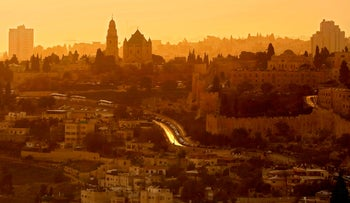 A general view taken from the Mount of Olives shows Jerusalem's Old City and the Abbey of the Dormition, as the sun sets during a sand haze. October 18, 2018