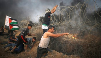 A Palestinian tries to remove Israeli wire during a protest calling for lifting the Israeli blockade on Gaza and demanding the right to return to their homeland, at the Israel-Gaza border fence in Gaza October 19, 2018.
