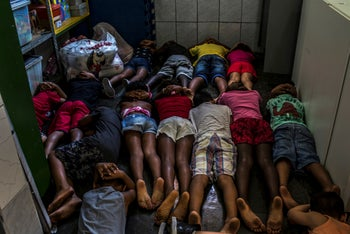Students practice taking cover during a drill at their school to prepare for the shootouts that frequently take place in the Maré favela in Rio de Janeiro, October 11, 2017