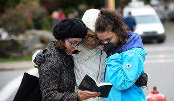 Women praying from a prayerbook a block away from the site of a mass shooting at the Tree of Life synagogue in Pittsburgh, October 27, 2018.