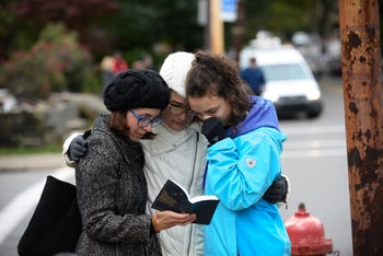Three women pray from a prayerbook a block away from the site of a mass shooting at the Tree of Life Synagogue in the Squirrel Hill neighborhood on October 27, 2018