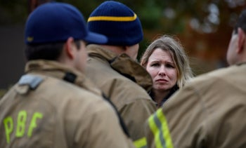 A woman asks for status update from Pittsburgh City firefighters near the site of the mass shooting at the Tree of Life synagogue on October 27, 2018.