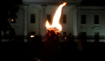 A candle burns as members and supporters of the Jewish community come together for a candlelight vigil in remembrance of victims of a shooting at a Pittsburgh synagogue, in front of the White House on October 27, 2018.