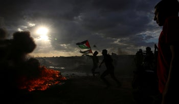 Protesters hurl stones while others burn tires near the fence of the Gaza Strip border, October 26, 2018.