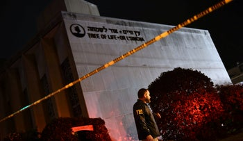 An FBI agent stands behind a police cordon outside the Tree of Life Synagogue after a shooting there left 11 people dead in the Squirrel Hill neighborhood of Pittsburgh on October 27, 2018