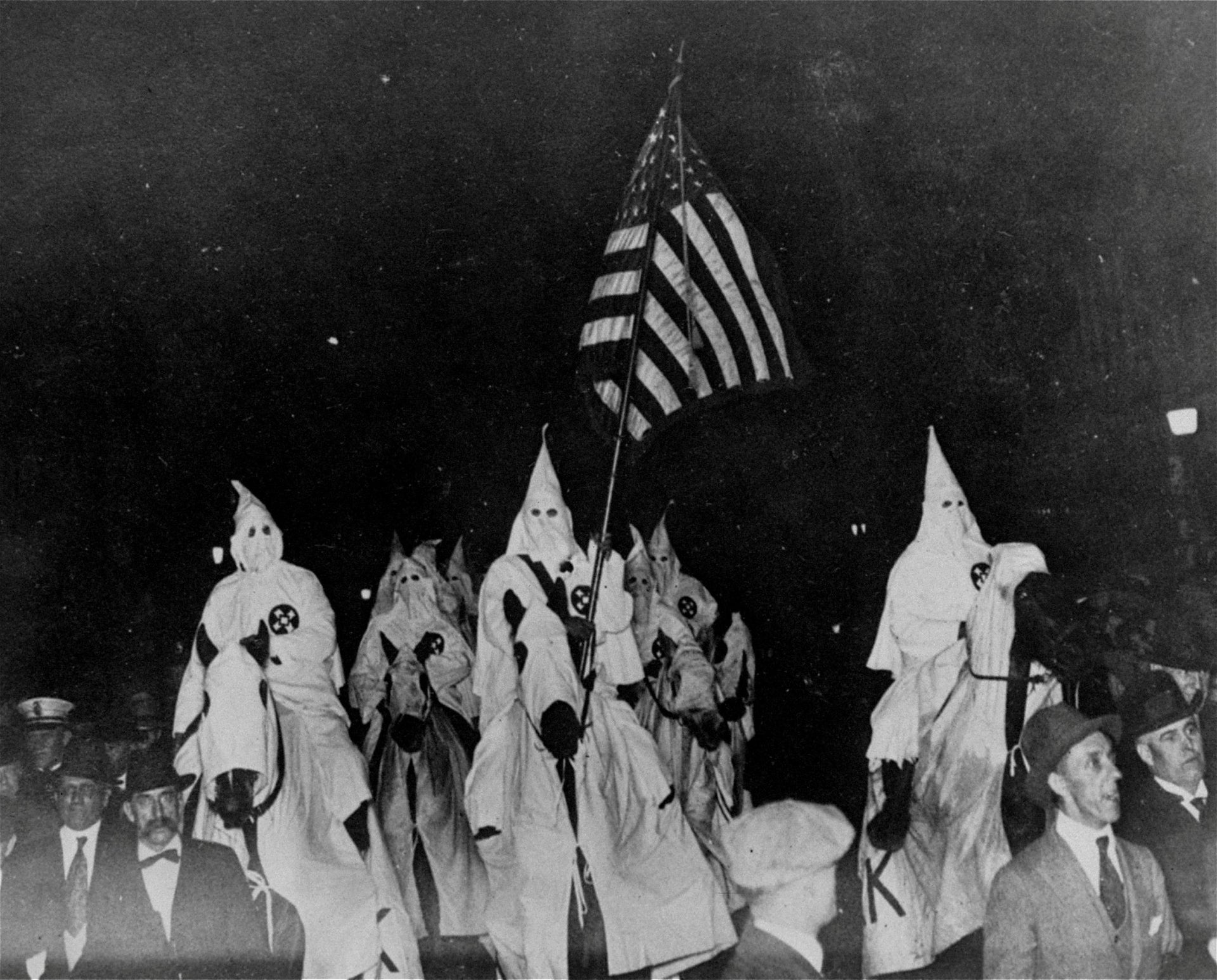 An unusual photo depicting the Ku Klux Klan in their regalia parading through the streets of Tulsa, Oklahoma, September 21, 1923, while the former Sheriff Bill  McCullough, whose efforts to stop the parade were fruitless, can be seen to the left of the hooded horse, note the uniformed police marching alongside the Klansmen.
