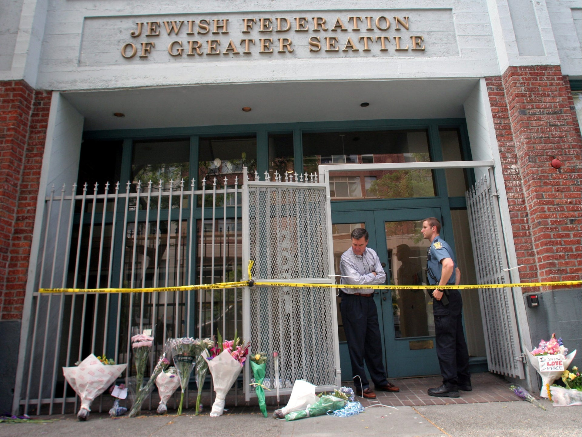 Seattle Police Chief Gil Kerlikowske, left, looks at flowers left by passersby at the Jewish Federation Building in Seattle, Saturday, July 29, 2006.