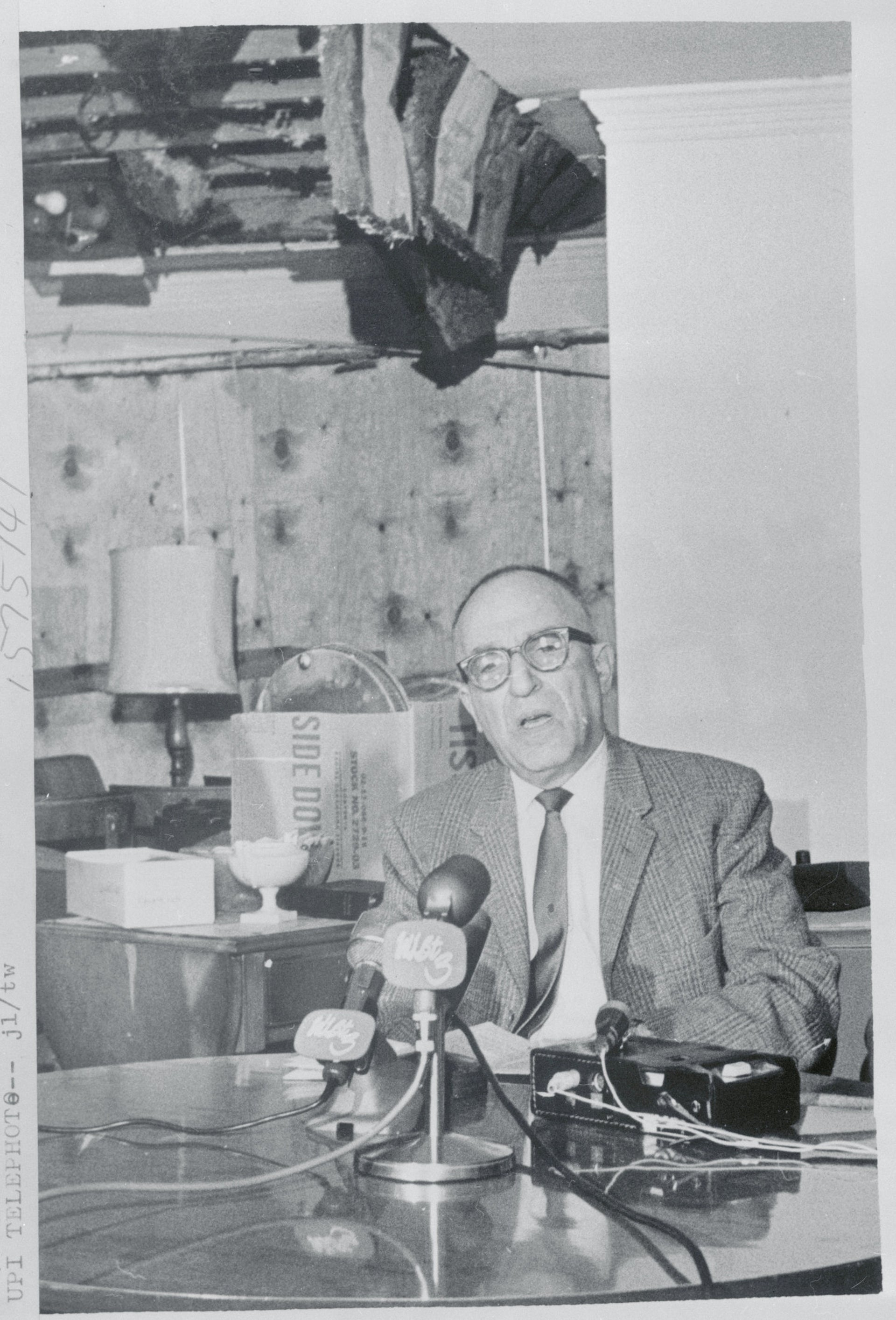 Rabbi Perry Nussbaum talking with newsmen in the living room of his home, which was firebombed on November 21, 1967.