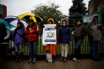 Deb Polk holding a sign as she gathers with others for a vigil in the aftermath of the deadly shooting at the Tree of Life Synagogue in Pittsburgh, October 27, 2018.