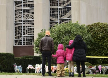 People stand in front of a memorial outside of the Tree of Life Synagogue, October 28, 2018.