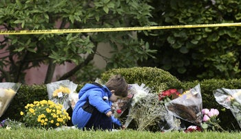 A boy places flowers on October 28, 2018 outside of the Tree of Life Synagogue after a shooting there left 11 people dead in the Squirrel Hill neighborhood of Pittsburgh on October 27, 2018.