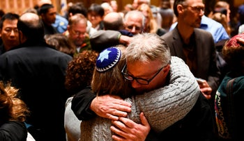 People hug after a vigil to remember the victims of the shooting at the Tree of Life synagogue, October 28, 2018.