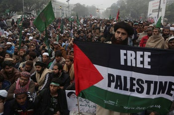 A man brandishes a Palestinian flag as supporters of Pakistani religious party rally against America in Lahore, Pakistan, Wednesday, Dec. 13, 2017