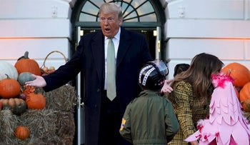 U.S. President Donald Trump reacts as U.S. first lady Melania Trump hands out Halloween candy to trick or treaters at the White House in Washington, U.S., October 28, 2018